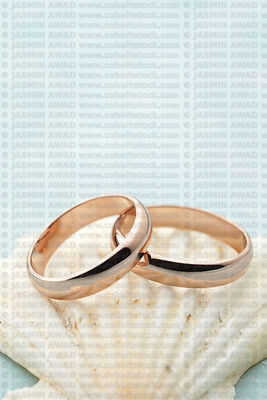 Rose gold wedding rings on seashell with blue wood background Vertical image with space for invitation text