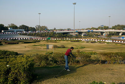 India - Delhi - A man uses a hosepipe to wash on a gardened Traffic Island