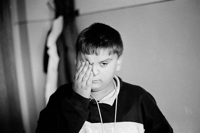 A boy holds his eyes that are sore after treatment