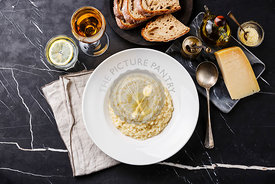 Risotto with parmesan cheese on plate on dark marble table background