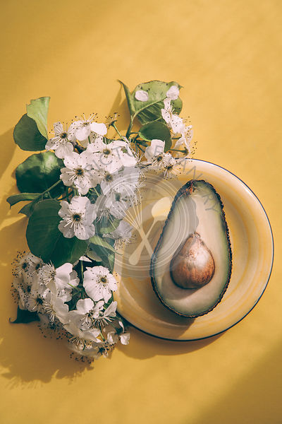Fresh avocado on a yellow background with flowers
