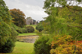 View through trees and shrubs over Round Pond towards Castle Kennedy ruin