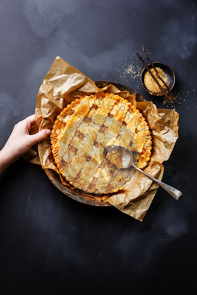 Lemon Pie and female hand on blackboard slate background copy space