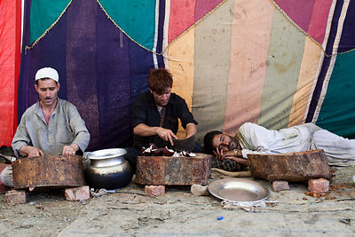 India - Srinagar - A Waza, a traditional Kashmiri cook, chops ingredients whilst his exhausted companion sleeps after cooking all night at a Wazwan feast.