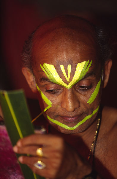 India - Kerala - Professor Balasubramanian, a senior teacher of Kathakali applies his make up before a performance
