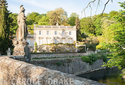 Iford Manor, a Georgian house, sitting in a steep sided valley beside the River Frome, seen from the bridge, dating from 1400, topped by an 18th century statue of Britannia installed by Peto. Iford Manor, Bradford-on-Avon, Wiltshire