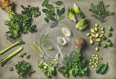 Flat-lay of whole and cut green vegetables and edible herbs