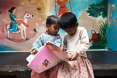 Girls read a book at the Amader Bari shelter operated by Child in Need Institute (CINI, ciniindia.org), Kolkata, India.