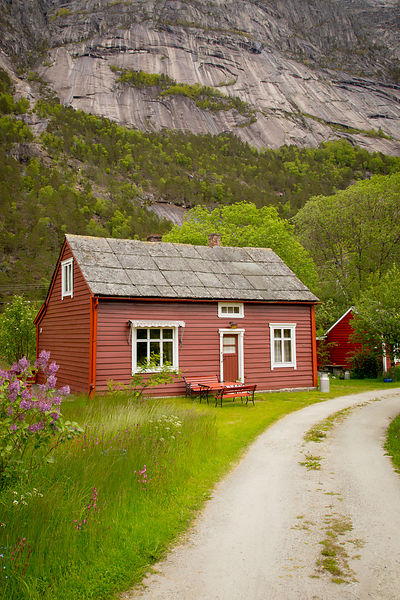 Small Red Norwegian House at the Foot Mountain in Summertime