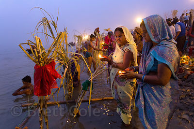 Ladies pray at sunset along the Ganges River during Chhath Puja, Varanasi, India. Chhath Puja is a devotion to the Sun God Surya in which people gather at sunset and then on the following sunrise and offer prayers.