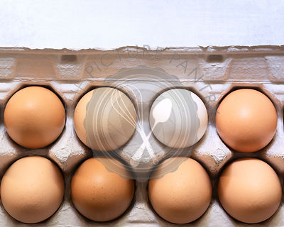 Close-up view of eggs in a cardboard carton.