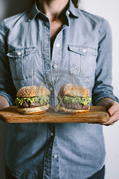 A woman is photographed from the front view while holding two guacamole burgers in her hand on a wood cutting board.