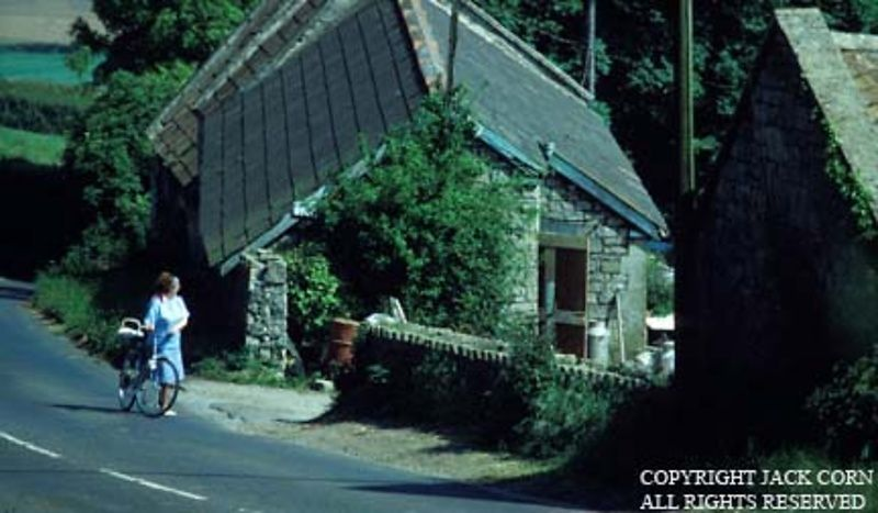 England, Lady pushes bicycle past farm