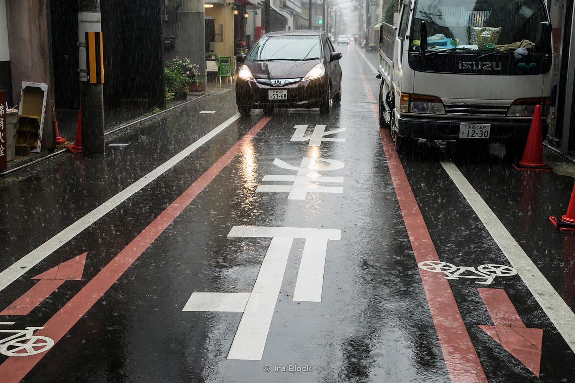 Stop sign on the road  near Nishiki Market in Kyoto, Japan during heavy rain.