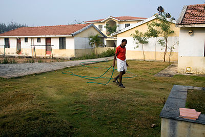 India - Cuddalore - An elderly resident waters the lawn