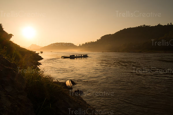 A water taxi drifts down the Mekong River at sunset. Luang Prabang, Laos