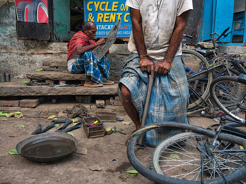 A worker at a bicycle shop repairs a cycle while the other one reads a newspaper