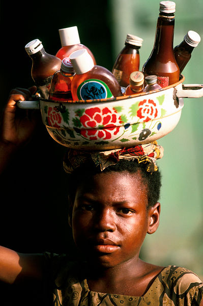 Ghana - Tamale - A street child selling bottles from a bowl on her head