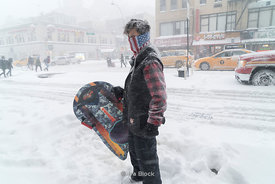 A boy looking for a place to go sledding in Chelsea, New York City during the bomb cyclone snow storm of 2018.