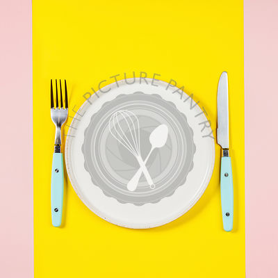 Flat lay of White plate, knife and fork on two color pastel background
