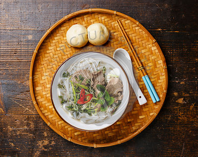Pho Bo vietnamese Soup with beef and steam bun Bao on bamboo tray on wooden background