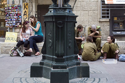 Israel - Jerusalem - Off duty soldiers  and two girls sit and talk on some steps in Ben Yahuda Street