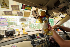 A taxi windshield covered with many stickers in Bangkok, Thailand.