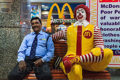 A police officer sits next to a life-size model of Ronald McDonald, Allahabad, India.
