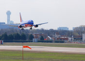 Southwest Airlines plane landing at Love Field in Dallas (downtown in background)