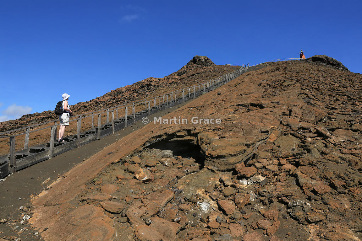 Tourist on the wooden steps to the summit viewpoint of Bartolome Island, Galapagos Islands