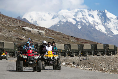 Tourists ride ATVs near a convoy of Indian Army trucks at Rohtang Pass, Manali, India