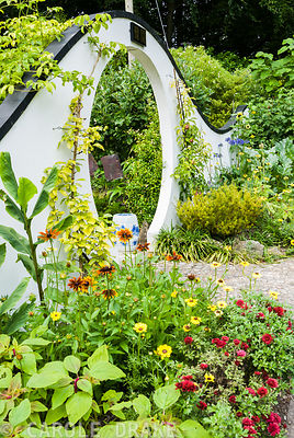 Moon gate marks passage from the kitchen garden to the Wandering Garden, framed by trained fruit trees, rudbeckias, agapanthus and sunflowers. Beggars Knoll, Newtown, Westbury, Wiltshire, UK