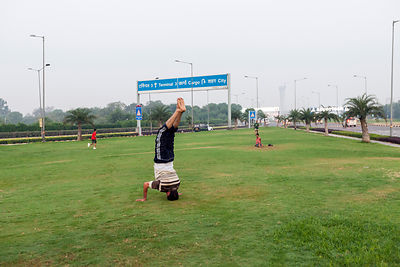 India - New Delhi - A man practices yoga on the private traffic greens at Aerocity near Terminal 3 of Indira Gandhi Airport,