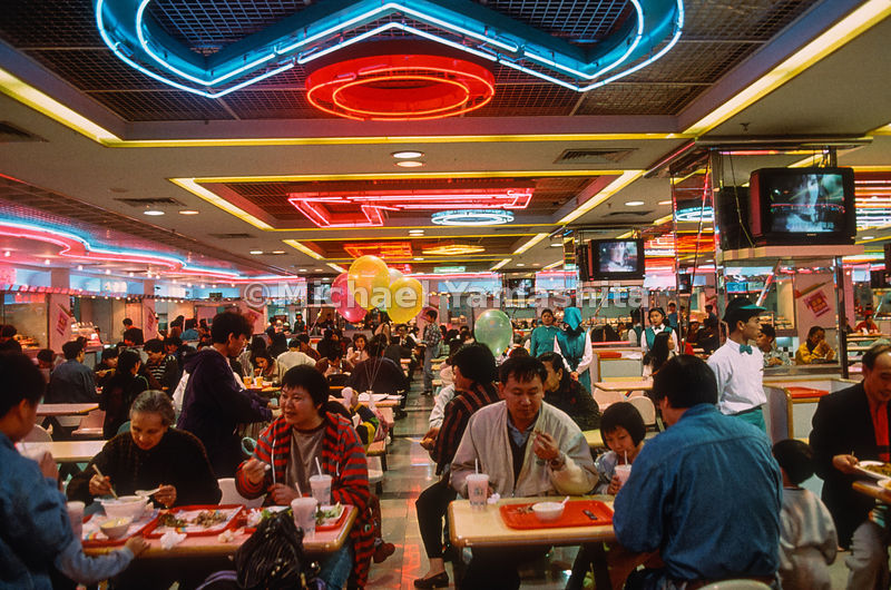 Fast learners at fast food, diners dig into noodles and burgers and watch Hong Kong TV at a Shenzhen food court.