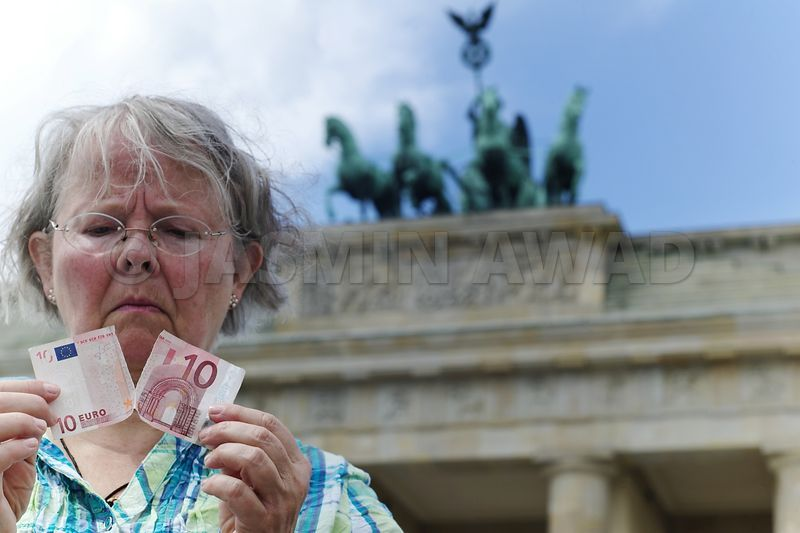 Eurocrisis senior lady with torn 10 euro bill