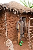 Disabled Rwandan man with a crutch outside his home. Rwanda