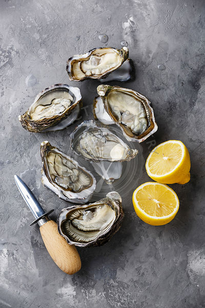 Open Oysters, lemon and knife on concrete background