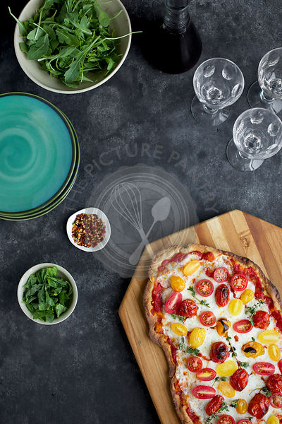 Roasted Tomato Pizza with a thin Olive Oil Cracker Crust.  Photographed on black/grey background from top view.
