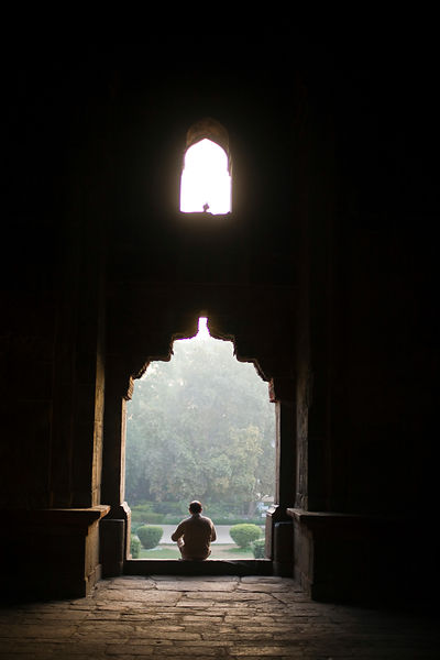 India - New Delhi - A man sits on the steps of the Bara Gumbad, Lodhi Gardens