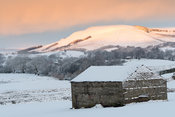 Old stone barn covered in snow after a storm in wensleydale, North Yorkshire, UK.