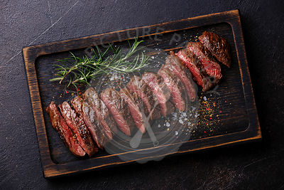 Sliced grilled meat barbecue steak Machete on dark background