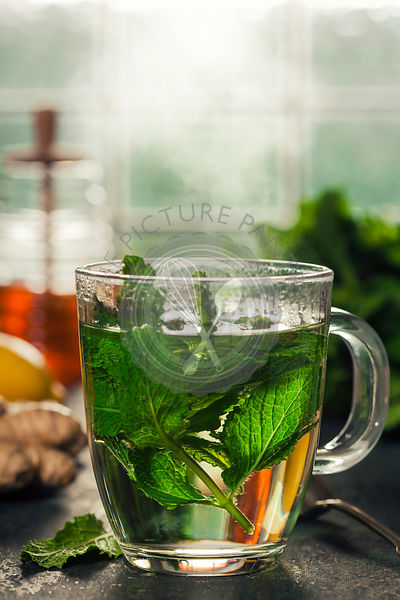 Fresh mint tea near the window. Cozy home or health concept