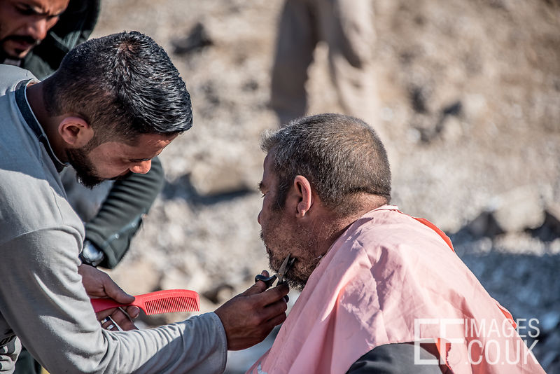 A Man Displaced From Mosul Gets His Beard Trimmed By A Barber At The Hamam al Alil IDP Camp
