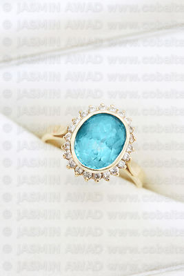 Elegant gold ring with blue topaz and diamonds in jewelry box