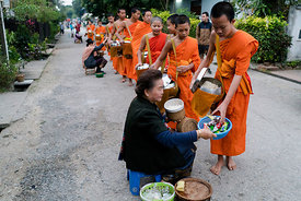 Early morning alms giving to monks in Luagprabang, Laos.