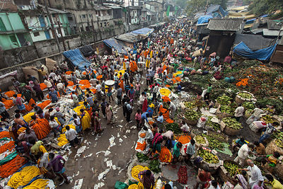 The main outdoor space at the Howrah Flower Market, commonly referred to as the largest flower market in Asia. Near Howrah Bridge along the Hooghly River, Kolkata, India.