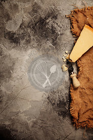 Food background with parmesan cheese over dark stone background. Lots of copy space