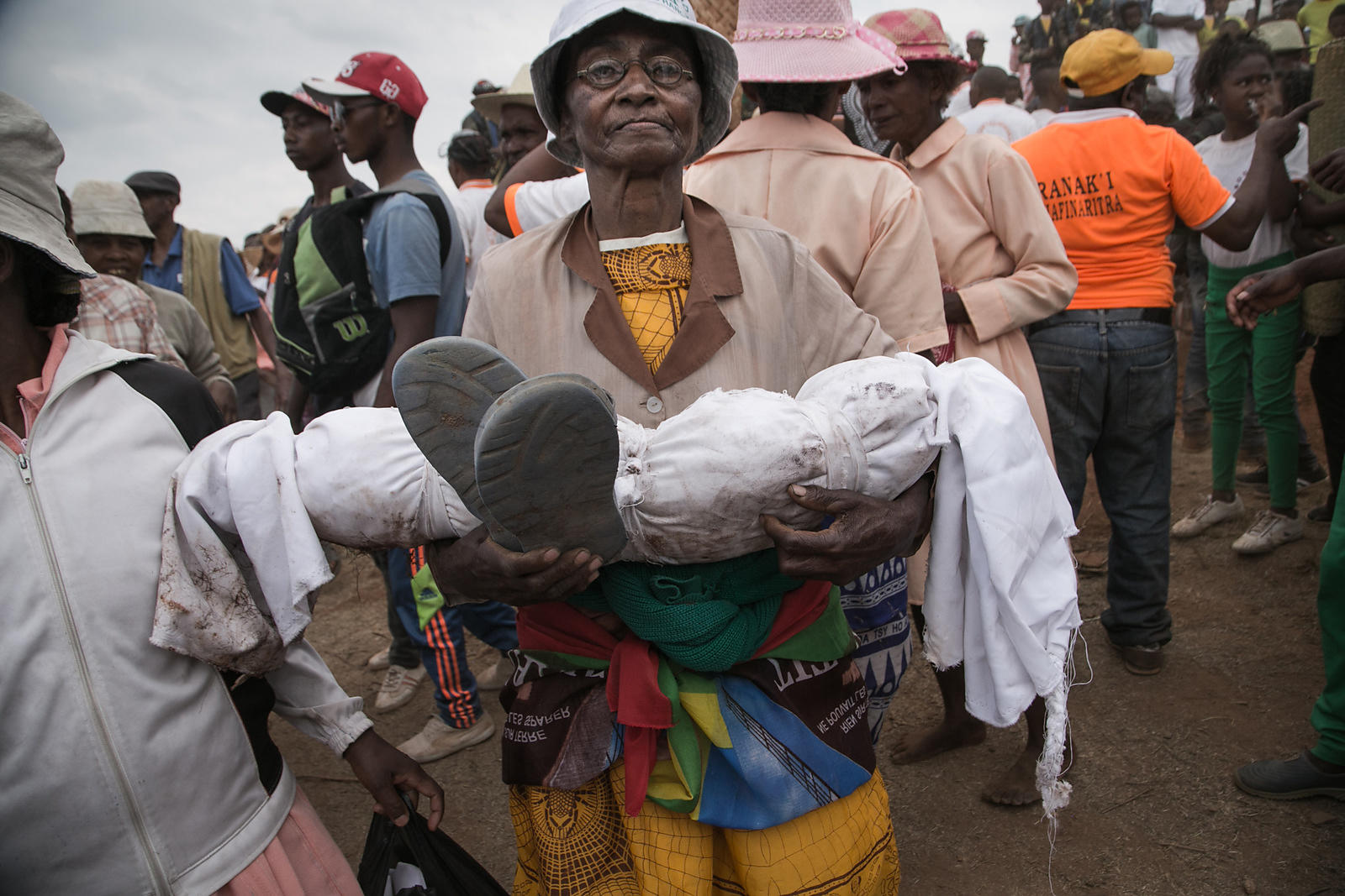 "Isabel Malala Razafindrakoto carries the wrapped body of her son, who died aged just three years old, as she takes part in a funerary tradition called the Famadihana in the village of Ambohijafy, a few kilometres from Antananarivo, on September 23, 2017. During the Famadihana, which can be translated as ""turning of the bones"", several crypts are opened and people take the bodies of their ancestors from the family crypts and rewrap them in fresh cloth, then dance with the corpses in their arms at the pace of traditional Malagasy band's music. The Famadihana is a pillar in the Malagasy ancestor's worship and is celebrated each three, five or seven years."