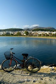 bicycle besides sea with town of rethymnon in distance, crete, greece.