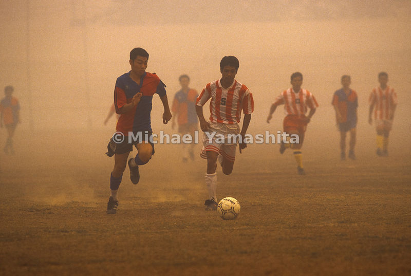 Men playing soccer in the haze from the aftermath of Indonesia's Plague of Fire.